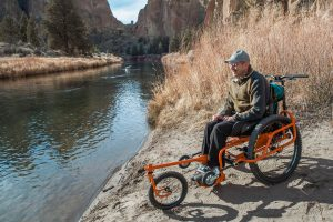 Geoff Babb sitting in the AdvenChair 2.0 along side a stream in Central Oregon