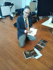Paul Sanders signs copies of his books while kneeling on the floor