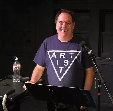 Michael Schutt wears a blue T-Shirt that says Artist as he stands a a music stand with a microphone and smiles at the camera