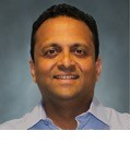 Sameer Bhide headshot against a bluish background