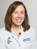 Dr. Laura Stein smiles at the camera while wearing a white doctor's coat against a gray back drop