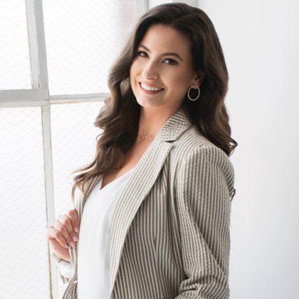 Jeri Ward wears a gray blazer in a white/off white room near as window. She has long, brown hair.