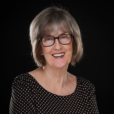 Jo Ann Glim sits in front of a dark background looking at the camera. She wears a black dress with white polka dots. She wears dark rimmed glasses