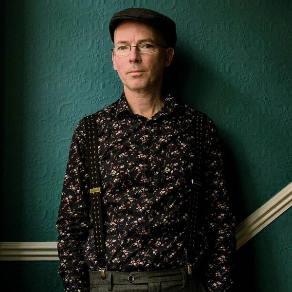 Author Jon McGregor wears a dark patterned shirt, suspenders, and a beret while standing against a dark green wall looking at the camera